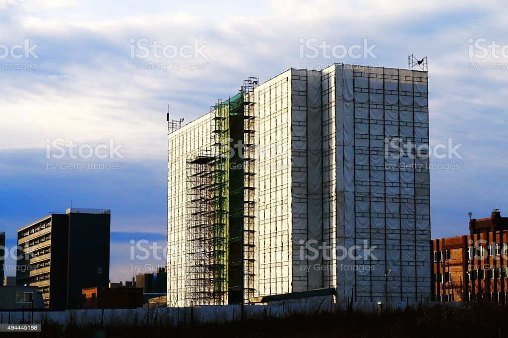Building construction site covered in a sheet stock photo