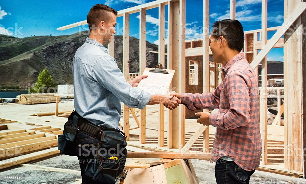 Building contractor giving handshake with man stock photo