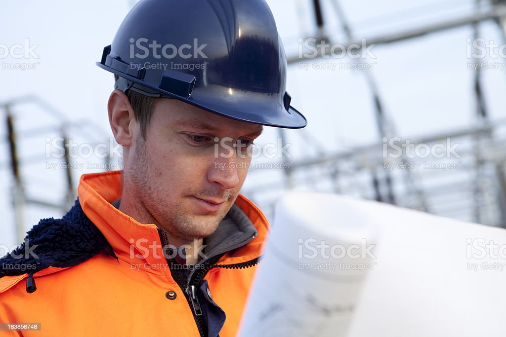 Building contractor is looking on his blueprint. stock photo