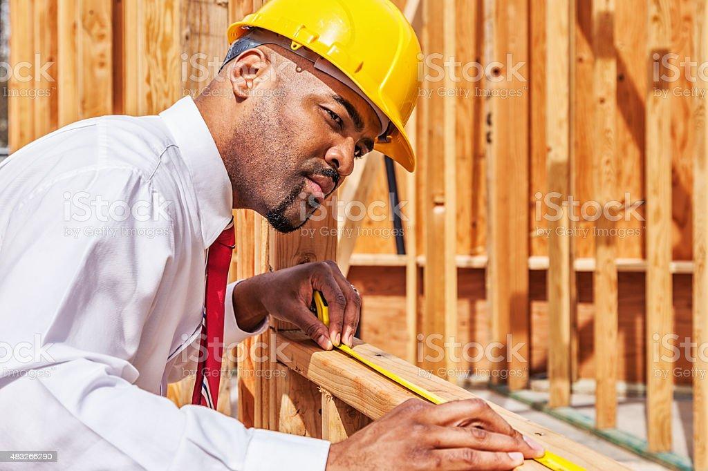 Building Contractor Measuring Wood Beam stock photo