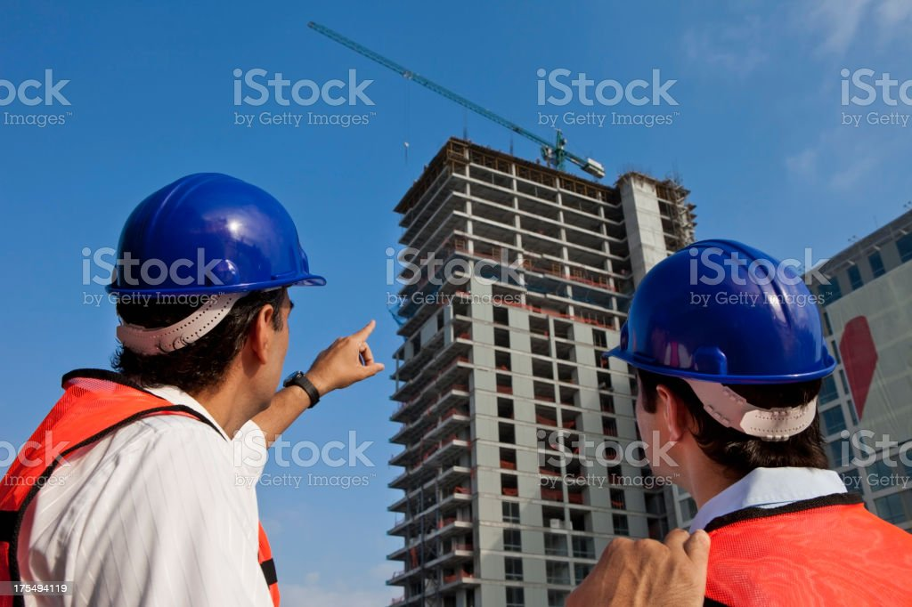Building Contractors Discussing Building Plans at a Construction Site