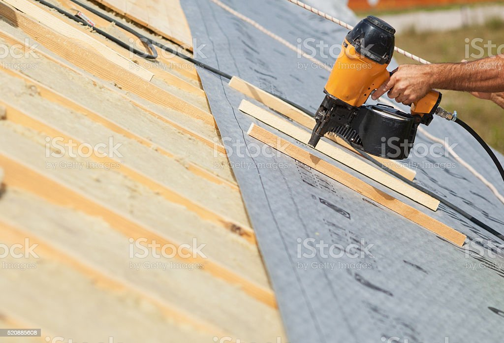 Building contractor worker (roofer) with air nail gun nailer working stock photo
