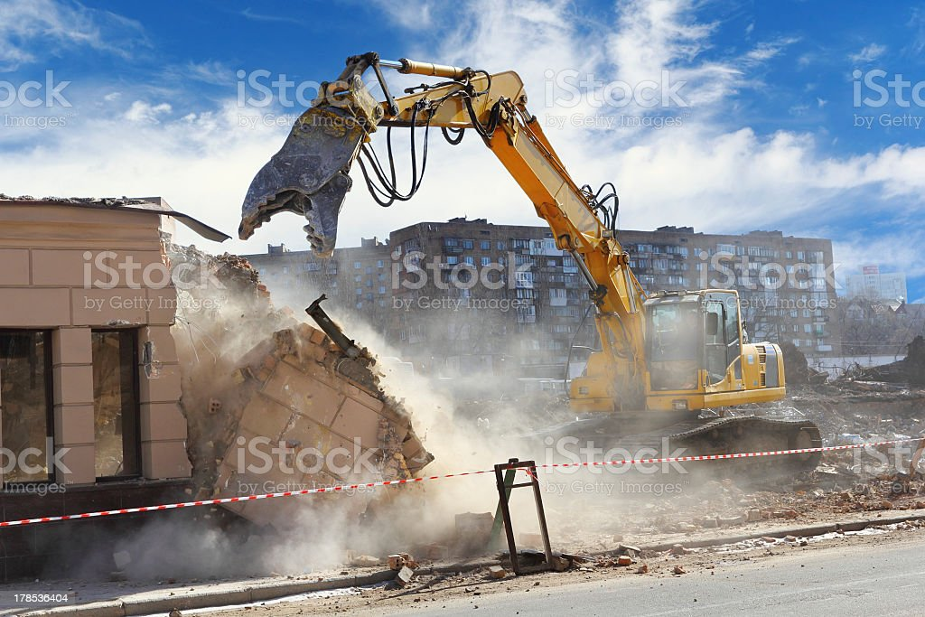 Building demolition machine pulls down a wall on a sunny day stock photo