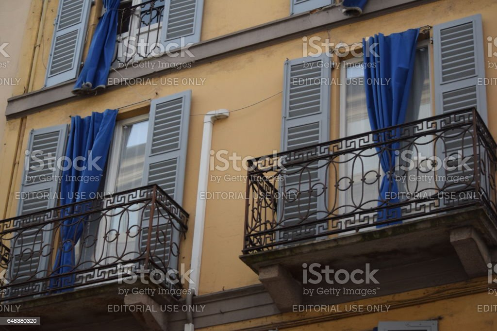 Building facade with balcony, shutters, windows door and external courtains stock photo