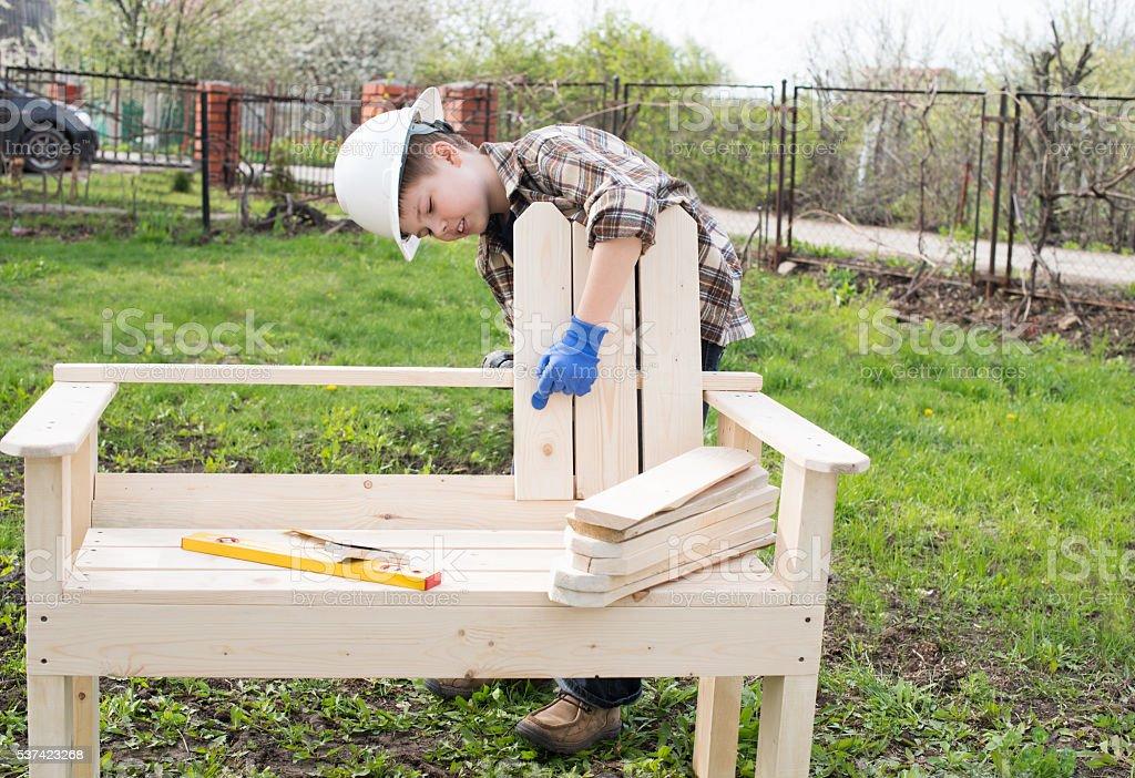 Building garden bench outdoors. Boy in helmet working. stock photo