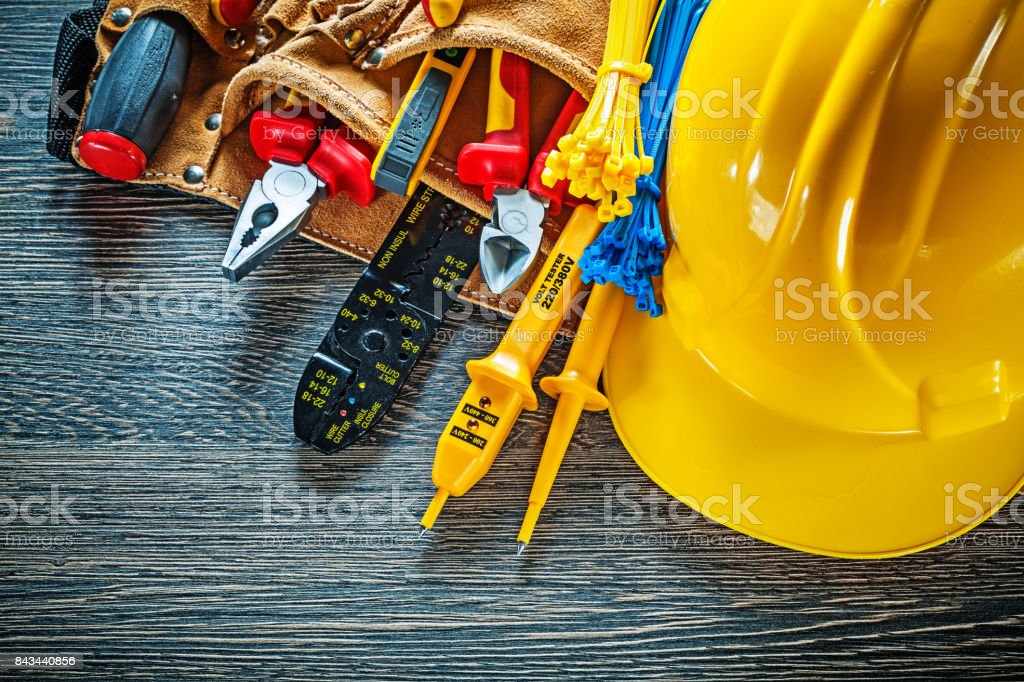 Building helmet leather tool belt on wooden board electricity co stock photo