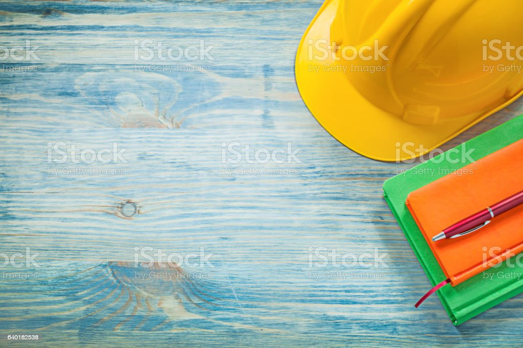 Building helmet notepads pen on wooden board construction concep stock photo
