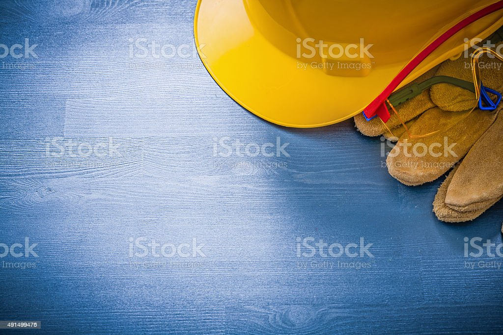 Building helmet safety glasses gloves on wood board construction stock photo