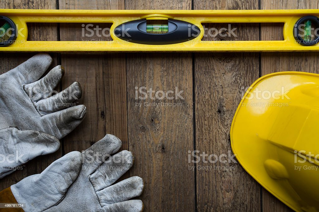 building level, helmat and glove on the old wood table stock photo