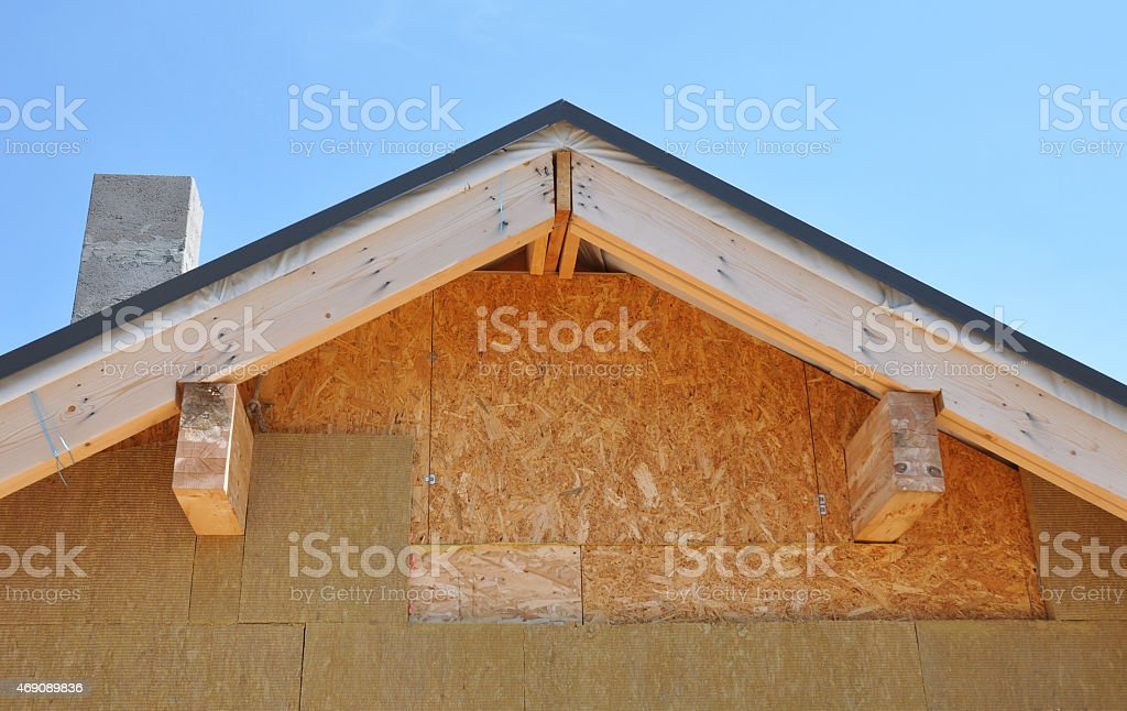 Building new house.Attic facade insulation against blue sky stock photo