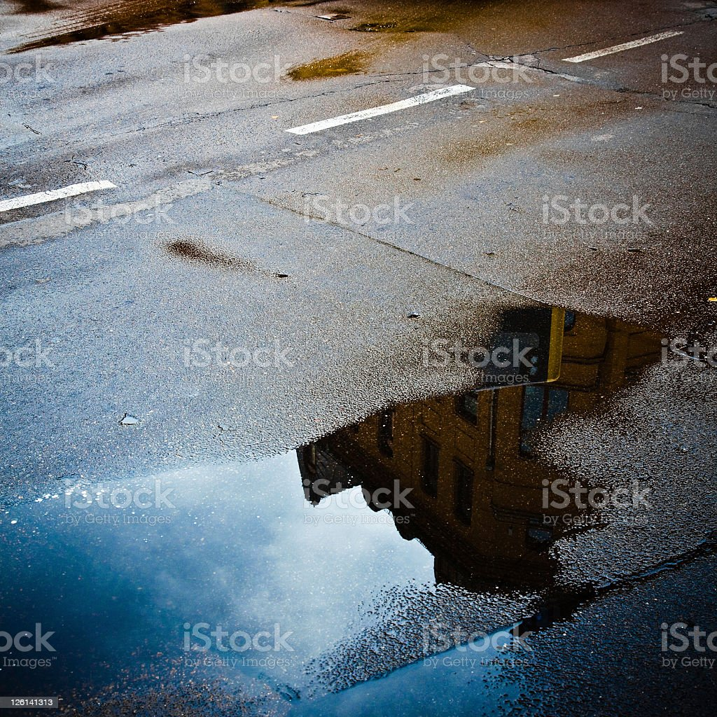Building reflected in puddle on the wet road stock photo