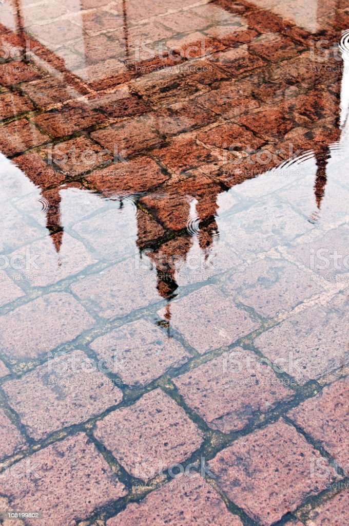 Building Reflection in Puddle on Brick Street. Color Image royalty-free stock photo
