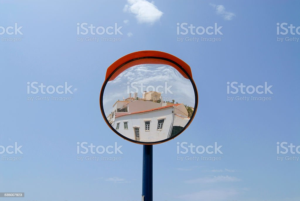 Building reflects in a street mirror in Ferragudo, Portugal. stock photo