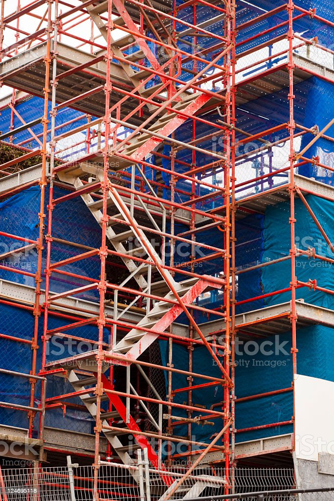 Building site with scaffolding and blue protective plastic sheet cover royalty-free stock photo