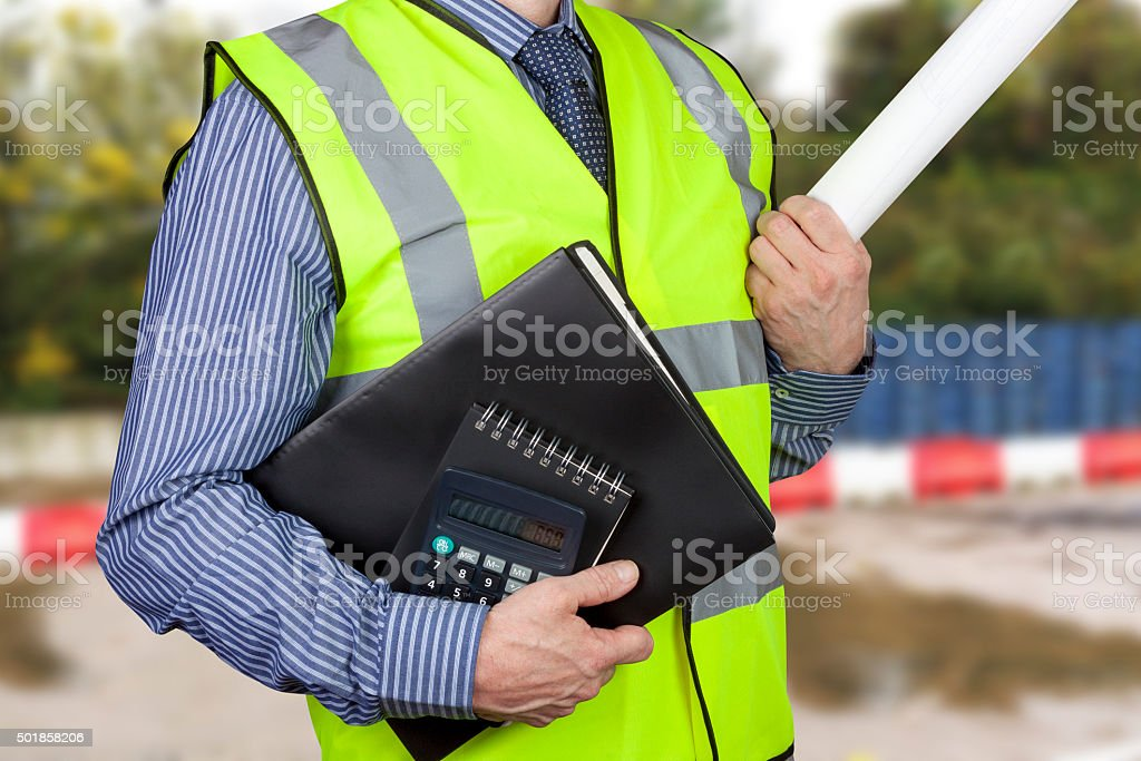 Building surveyor in hi vis carrying work folders and calculator stock photo