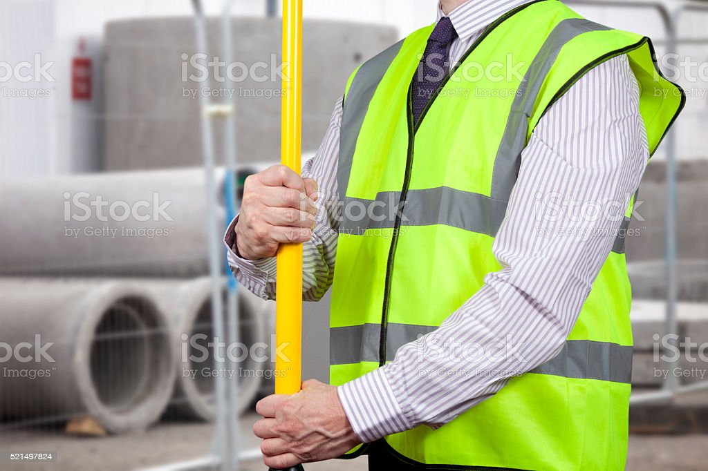 Building surveyor in high visibility adjusting tripod stand stock photo