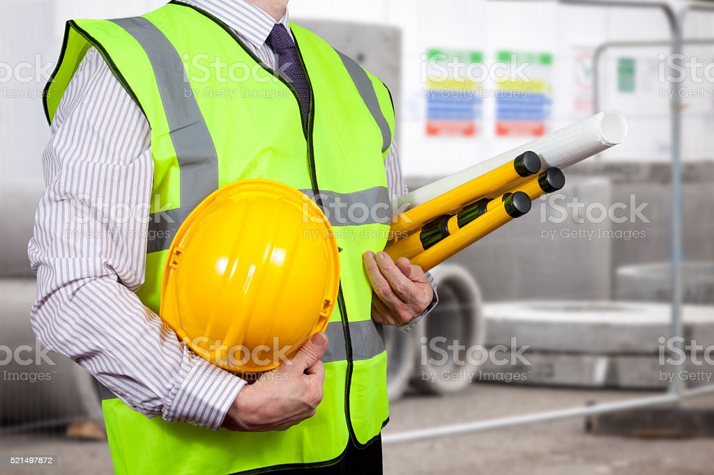 Building surveyor in high visibility carrying a tripod stock photo