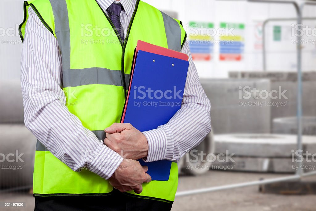 Building surveyor in high visibility carrying clipboard on site stock photo
