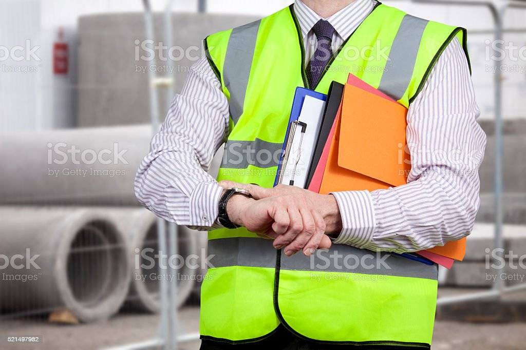 Building surveyor in high visibility checking the time on site stock photo