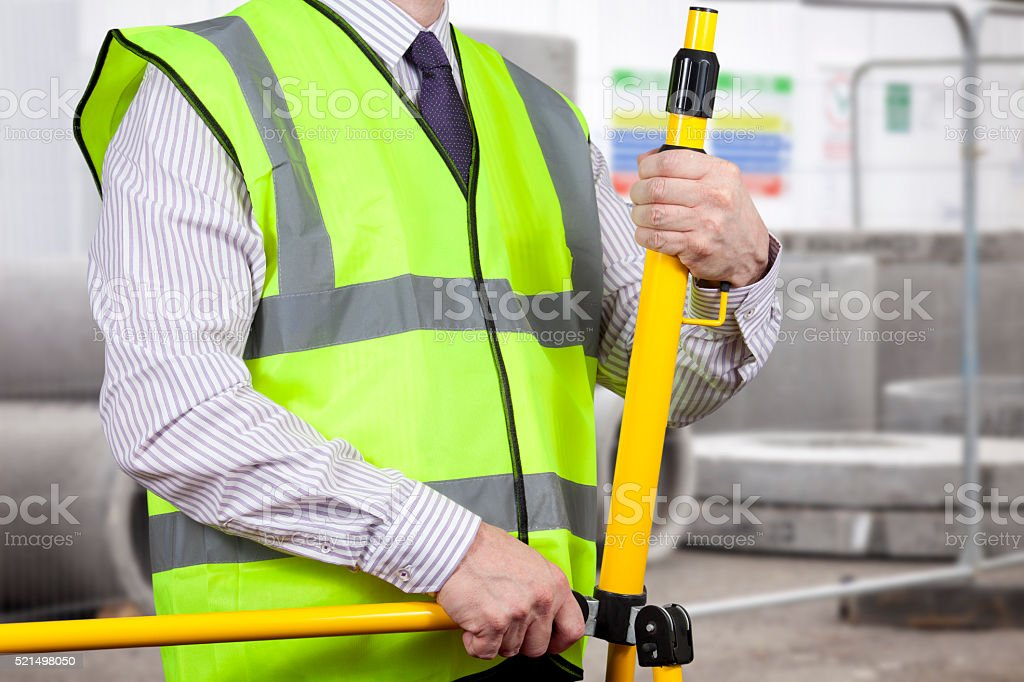 Building surveyor in high visibility setting up tripod stock photo