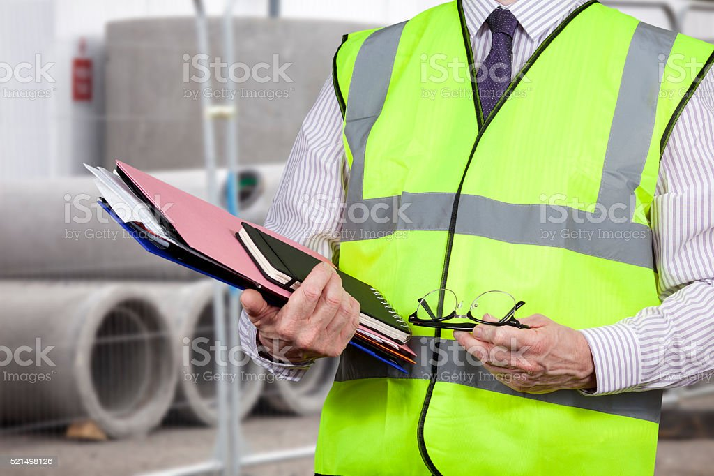 Building surveyor in high visibility vest carrying work folders stock photo