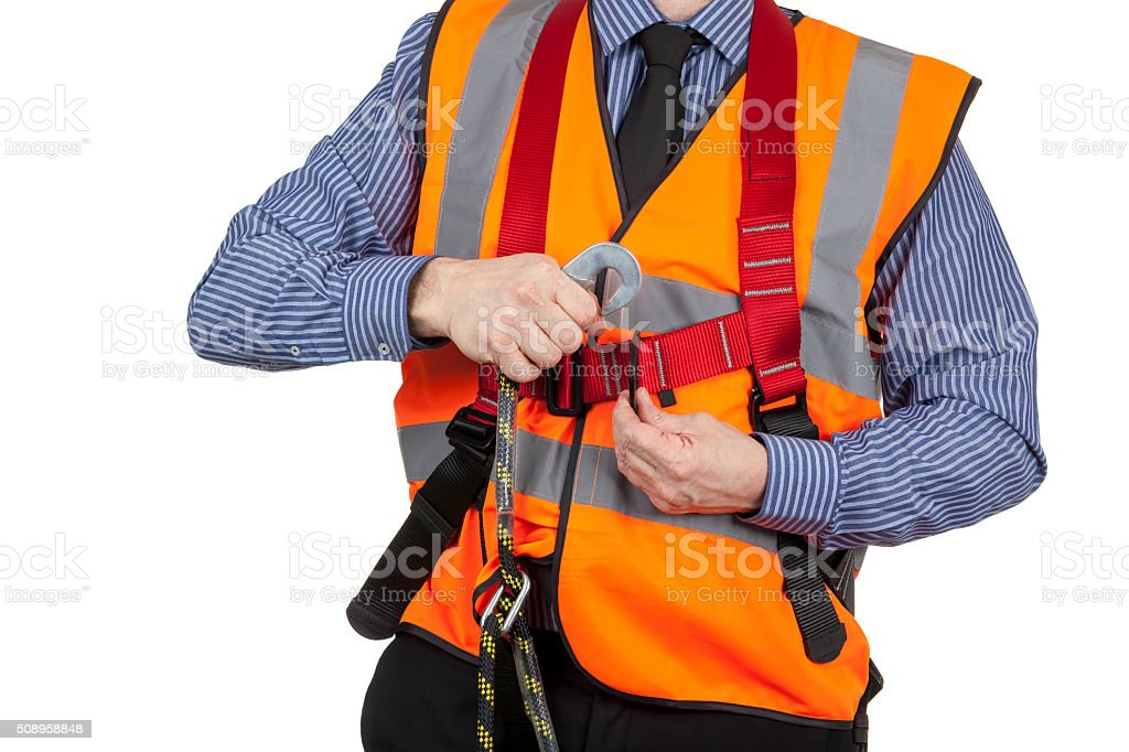 Building Surveyor in orange visibility vest attaching lanyard stock photo