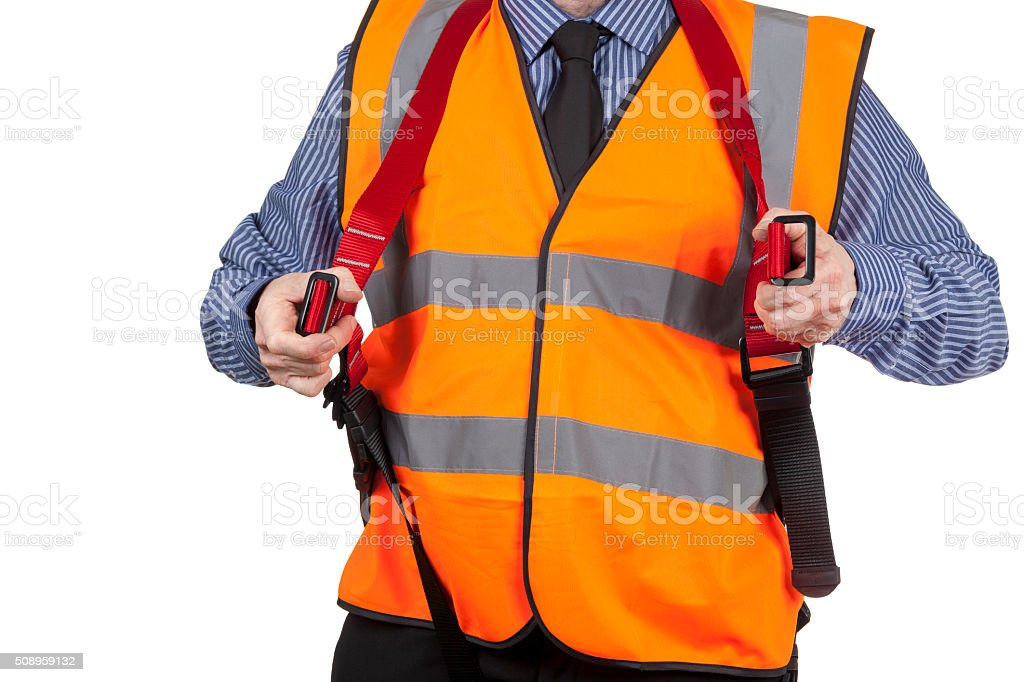 Building Surveyor in orange visibility vest putting harness on stock photo