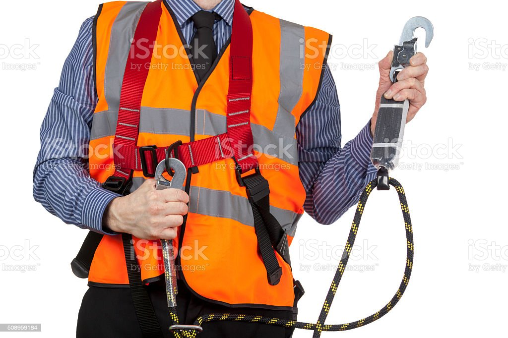 Building Surveyor in orange visibility vest securing safety  harness stock photo