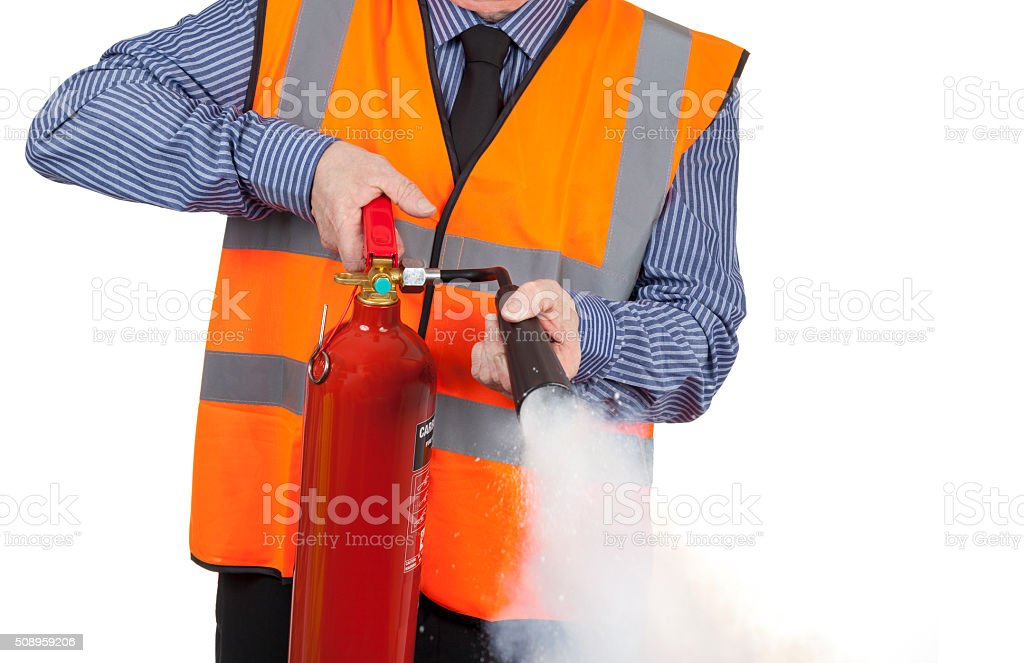 Building Surveyor in orange visibility vest using a fire extinguisher stock photo