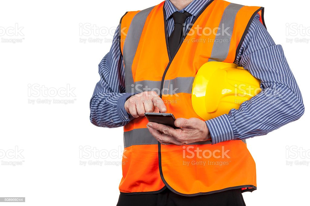 Building Surveyor in orange visibility vest using his smartphone stock photo