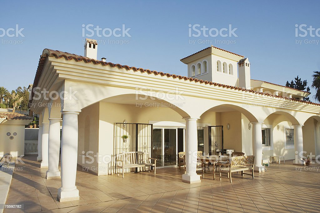 Building with columns and patio furniture on pool deck royalty-free stock photo
