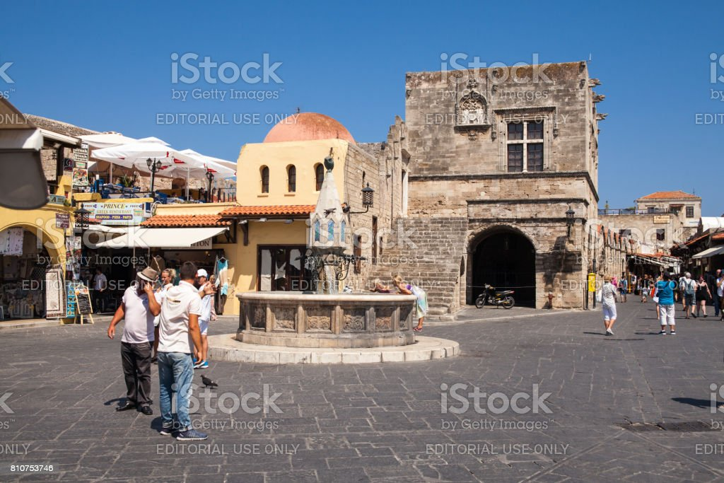Buildings and fountain in square houses of the locals and narrow streets in the city center in the Old Town of the capital of the island of Rhodes. Typical Greek style and building. stock photo