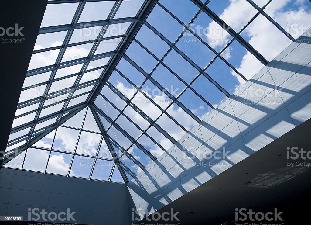 A building's glass roof facing a blue sky with clouds stock photo
