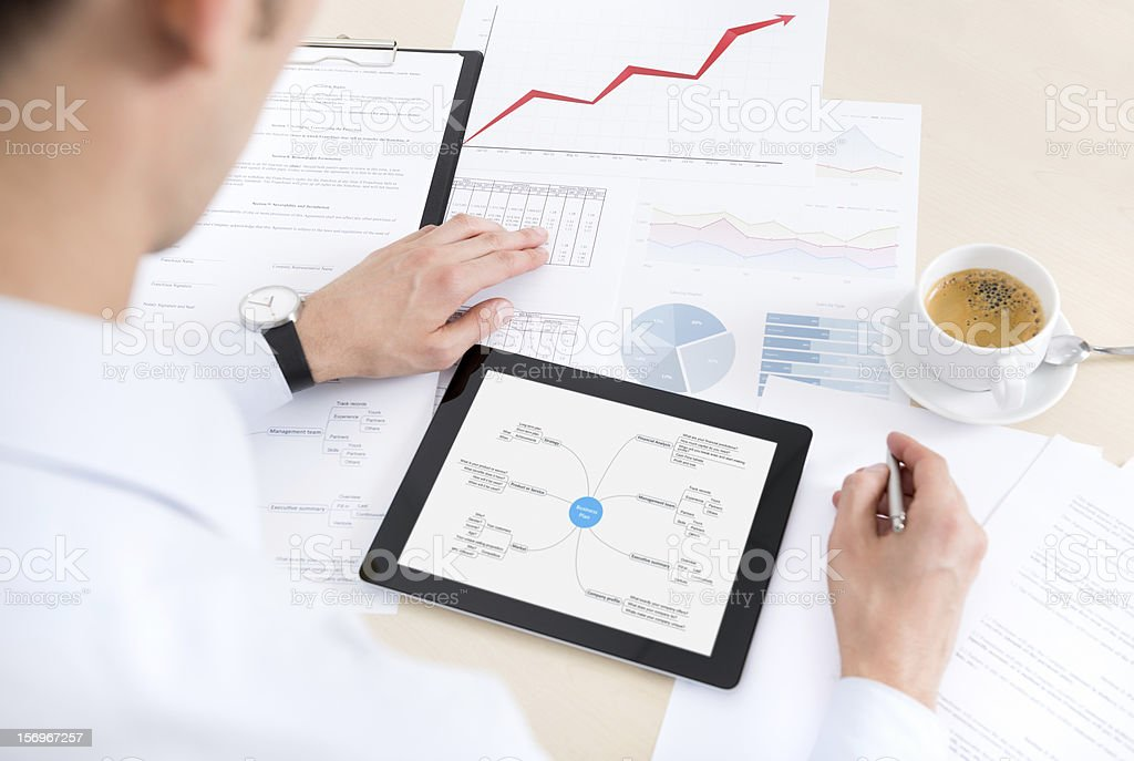Buinessman with tablet and documents at work royalty-free stock photo