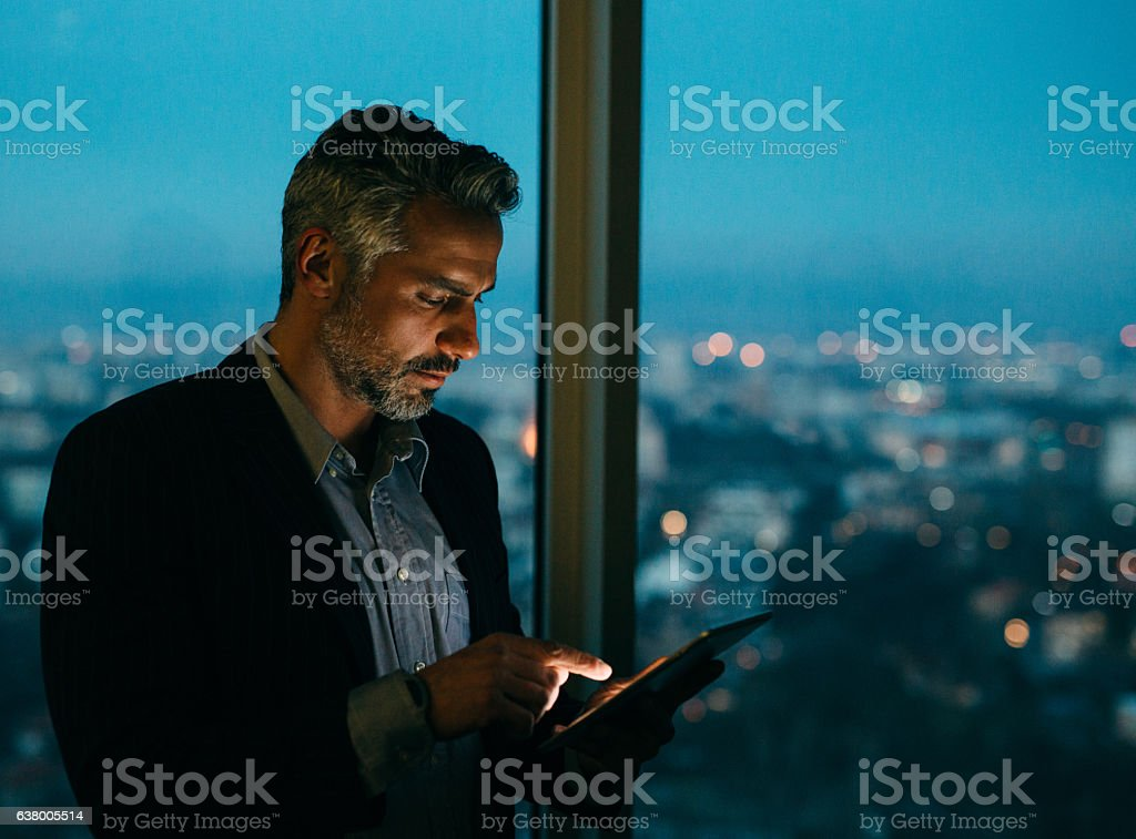 Buisnessman Using Tablet At Night stock photo
