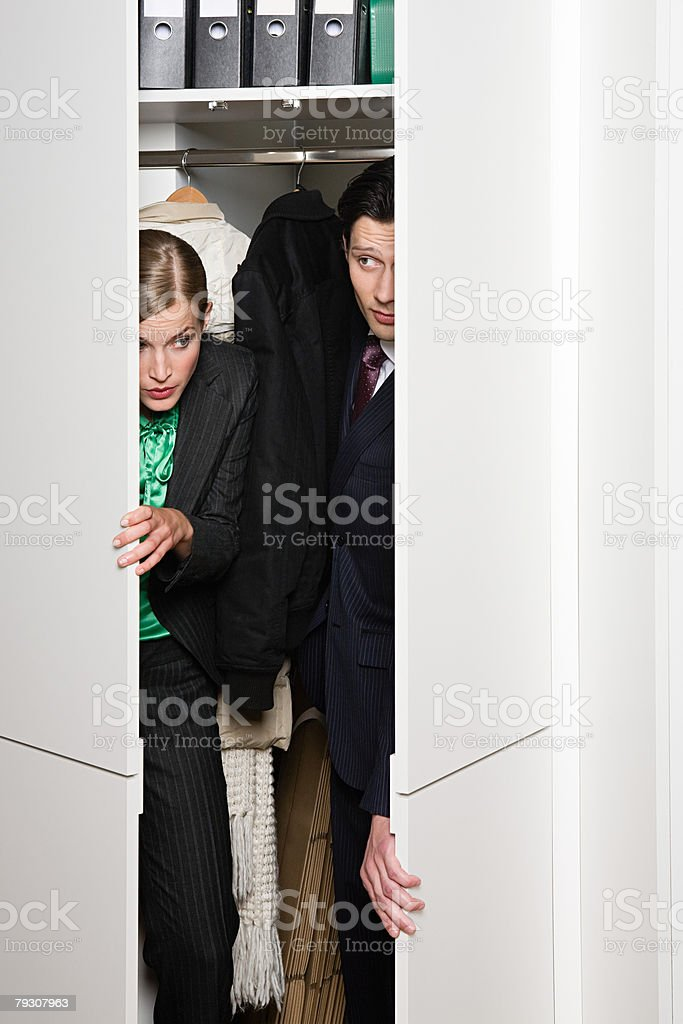Buisnesswoman and man sneaking out of closet stock photo