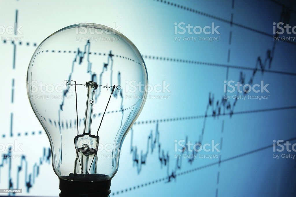 Bulb in front of a line graph chart background stock photo