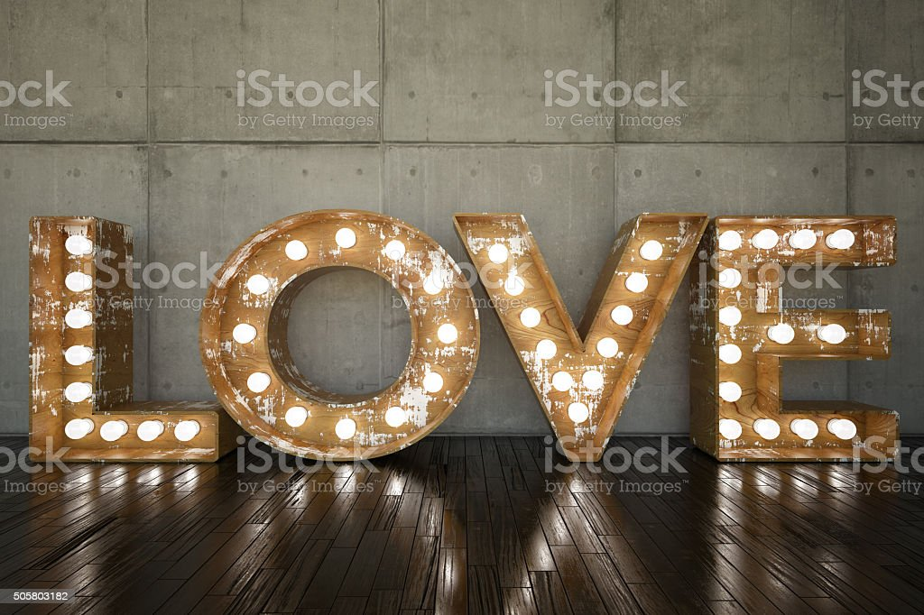Lightbulb sign with LOVE against wall