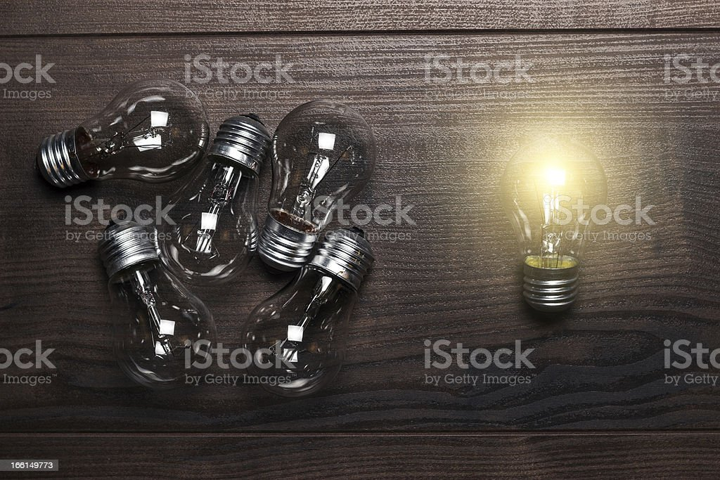 bulbs uniqueness concept on wooden background royalty-free stock photo