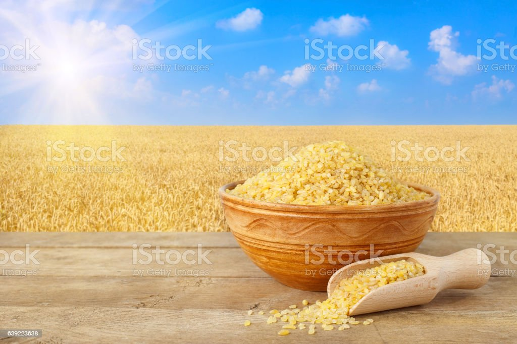 Bulgur in bowl on nature background stock photo