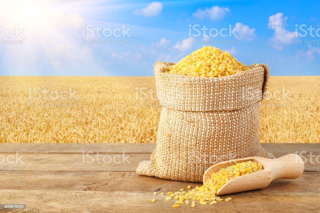 Bulgur in sack on nature background stock photo