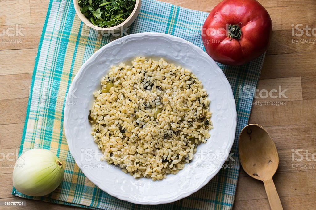 Bulgur rice served with wooden spoon stock photo