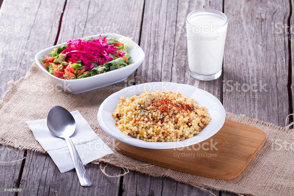 Bulgur with ayran and salad.selective focus on wooden background, kuskus stock photo