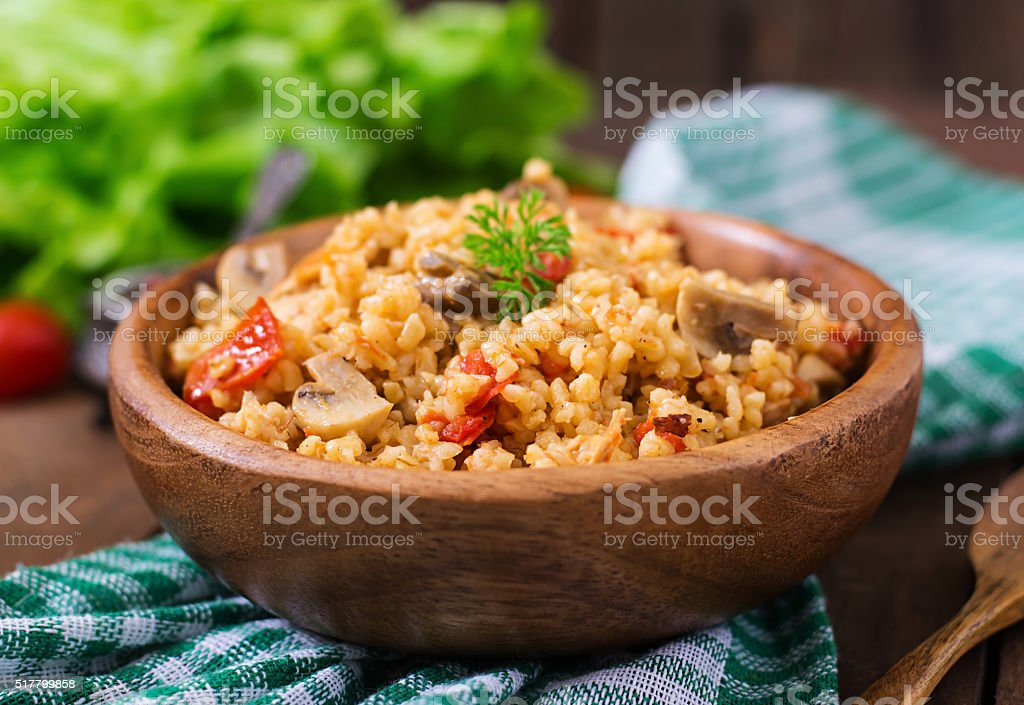 Bulgur with chicken, mushrooms and tomatoes in a wooden bowl. stock photo