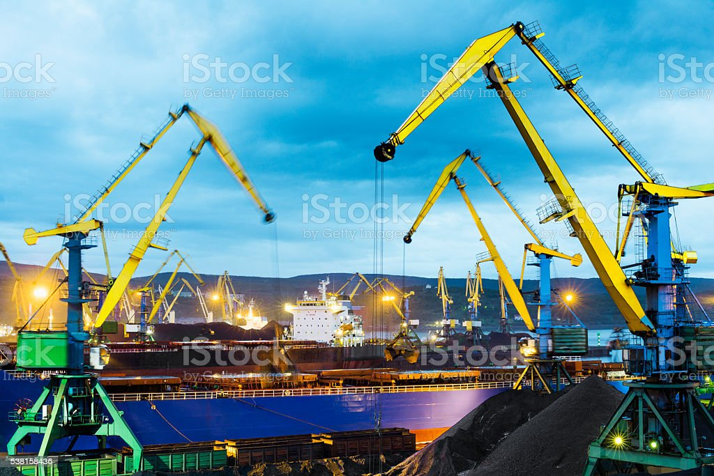 Bulk carriers, portal cranes, loading  coal in  seaport at evening. stock photo