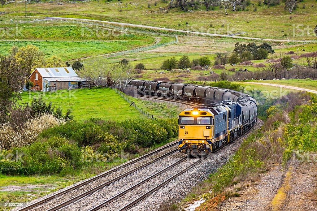 Bulk grain train rounding bend in lush rural landscape stock photo