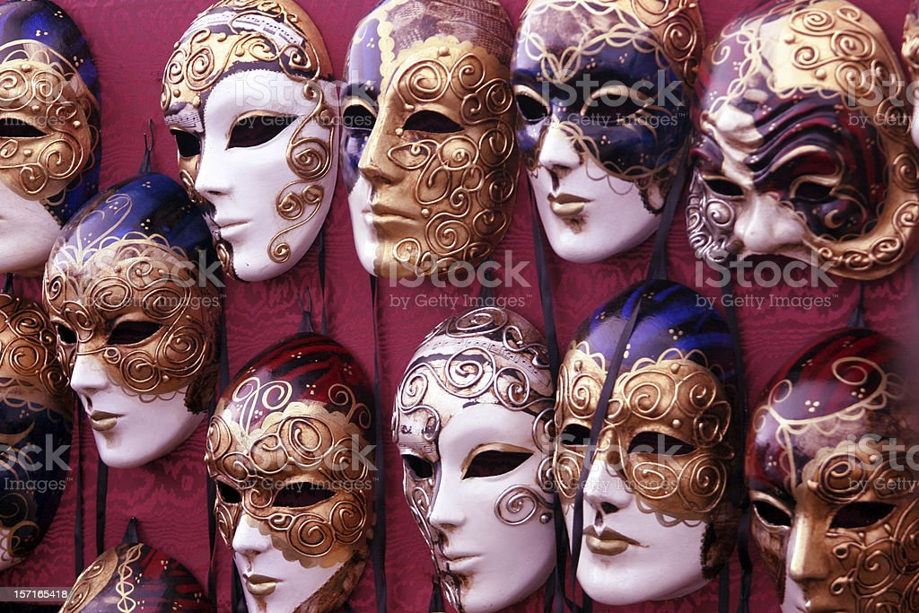 Bulk of venetian masks hanging in a row royalty-free stock photo