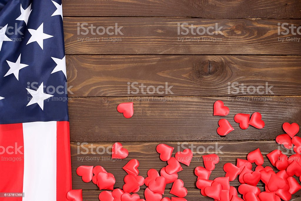 Bulk red hearts and USA flag, on a wooden table. stock photo