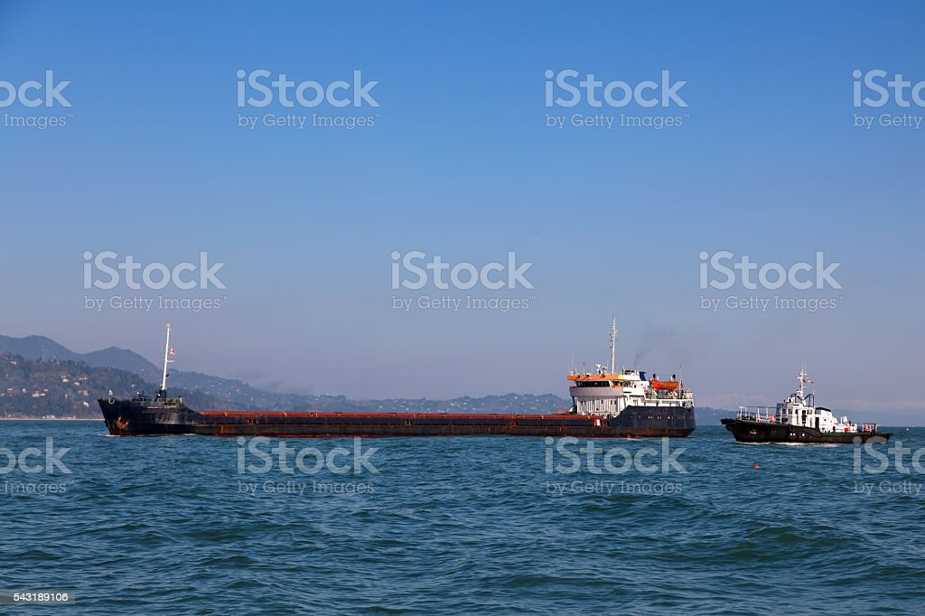 Bulk-carrier ship and tugboat stock photo