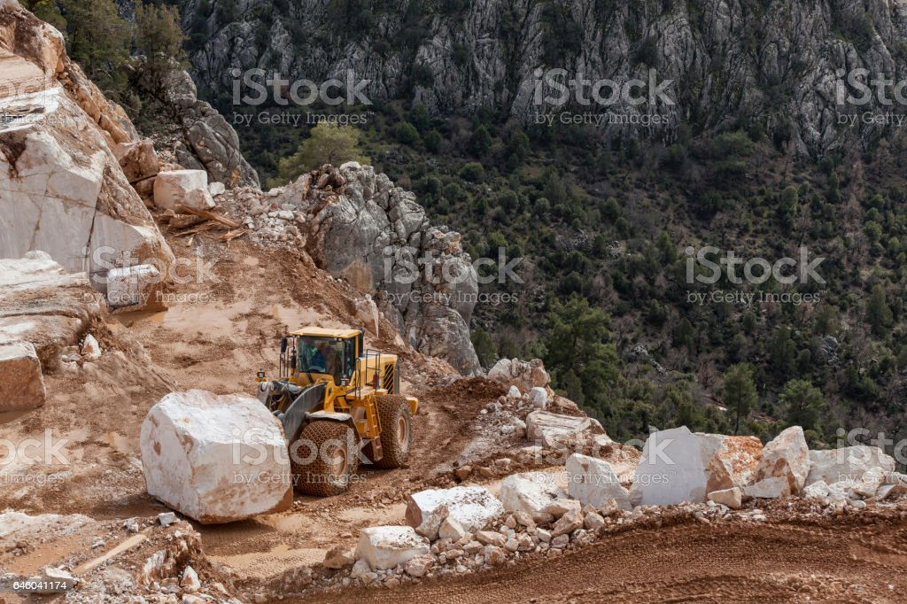 Bulldozer carrying oversized marble block in Quarry stock photo